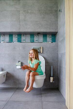 Feliz linda chica sentada en el inodoro en casa Foto de archivo