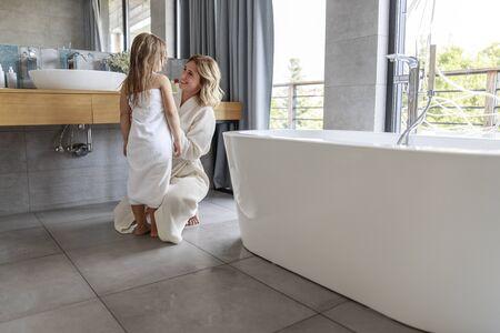 Madre en bata de baño en el baño en casa