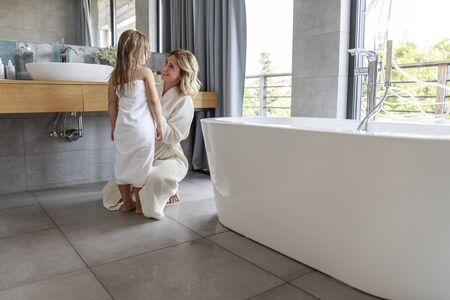Mother in bathrobe in bathroom at home