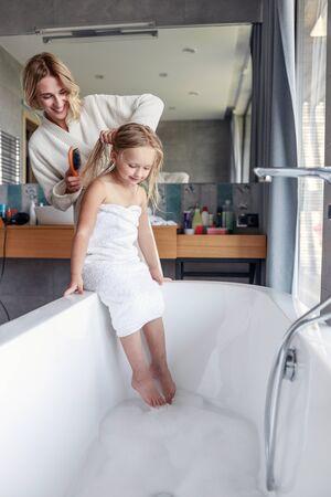 Süßes Mädchen mit nassen Haaren im Badezimmer Standard-Bild
