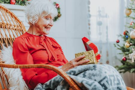 Happy old woman is holding gift box Standard-Bild - 129550100