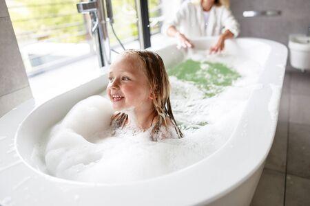 Smiling cute girl swiming in the bath