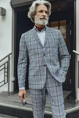 Bel signore elegante in piedi per strada Archivio Fotografico