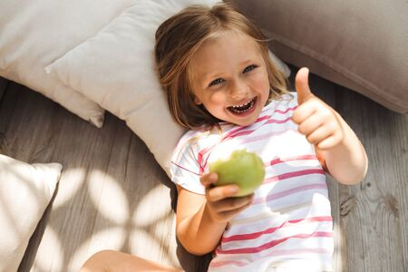 Excited kid with apple putting thumb up stock photo