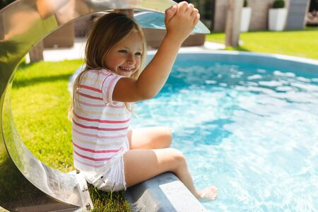 Excited girl under the metal shed near pool stock photo