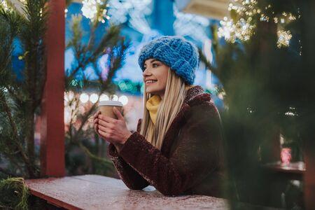 Dreamy blonde female person enjoying hot beverage
