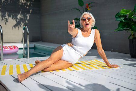 Fröhliche alte Frau, die sich am Swimmingpool ausruht Standard-Bild