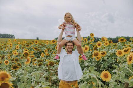Cheerful Caucasian man looking at camera in sunflower field Standard-Bild