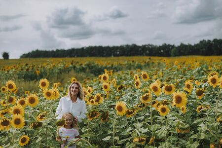 Happy family standing in the field of sunflowers Standard-Bild