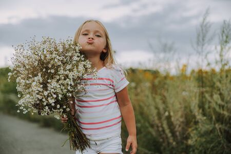 Pretty little girl is holding bouquet of flowers