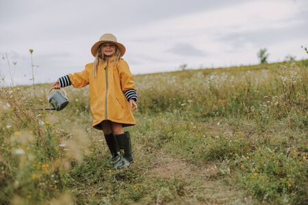 Smiling little girl is wearing hat outdoors