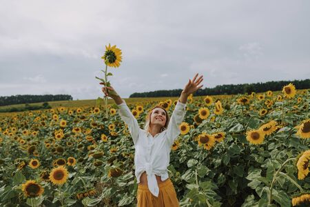 Happy girl walking in sunflower field in summer