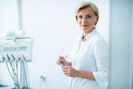 Female dentist is stanting in dental office Foto de archivo