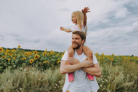 Happy cheerful daughter sitting on her smiling dads shoulders outdoors