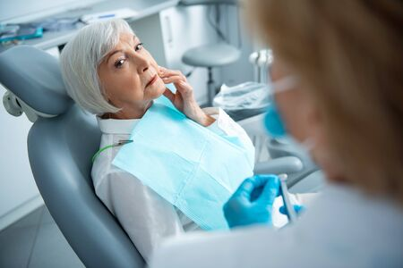 Adult woman with toothache sitting in dental chair Stockfoto