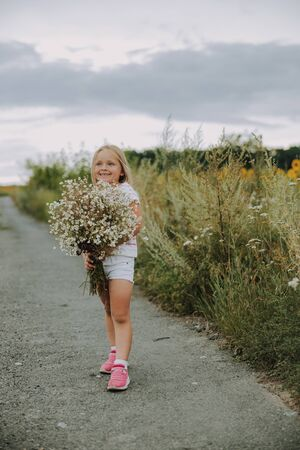 Happy little girl with beautiful wildflowers outdoors 写真素材
