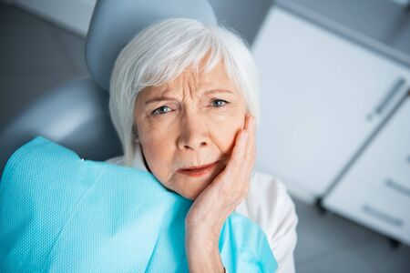 Upset adult woman with toothache in clinic
