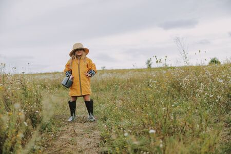 Little girl in rubber boots and raincoat