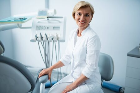 Smiling doctor is sitting in dental clinic