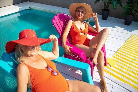 Two mature women resting by the swimming pool Imagens