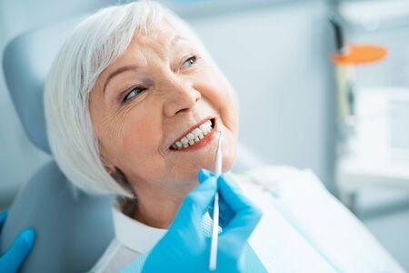 Smiling mature lady having a checkup at dentist