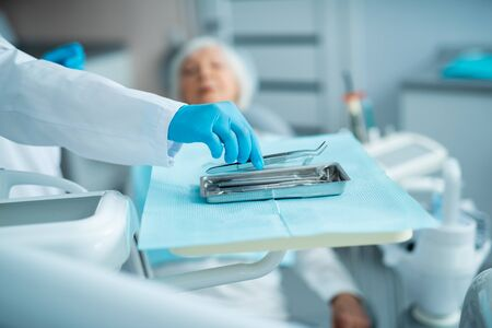 Dentist in sterile gloves taking dental surgical instruments Stock Photo