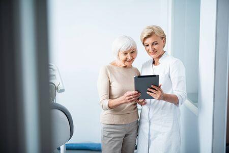 Volwassen vrouw en arts in tandartspraktijk