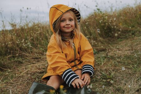 Smiling little girl is wearing raincoat outdoors
