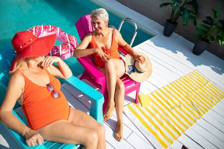 Cheerful senior women sitting in plastic chairs and talking