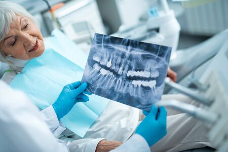 Happy adult female is looking on x-ray Foto de archivo