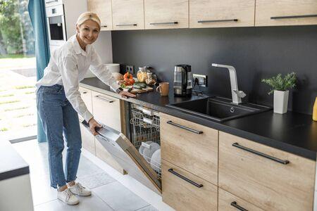 Happy woman opening door of the dishwasher