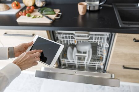 Woman including dishwasher and using a tablet