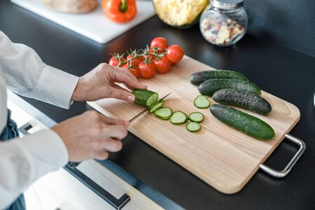 Lady slicing vegetables for salad in the kitchen 写真素材