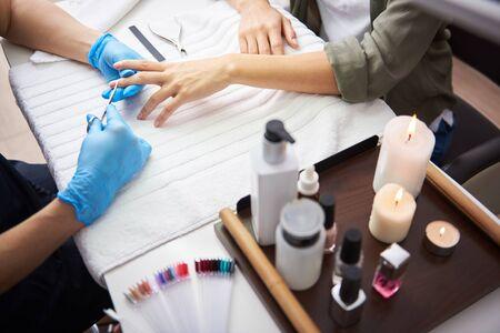 Maestro de manicura quitando la cutícula en los dedos de la dama con unas tijeras