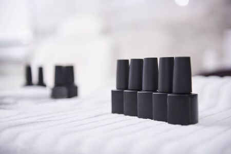 Black bottles of nail varnish on white soft towel Imagens