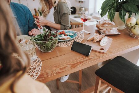 Family sitting at the table with salad, fresh vegetables, bread and cellphone