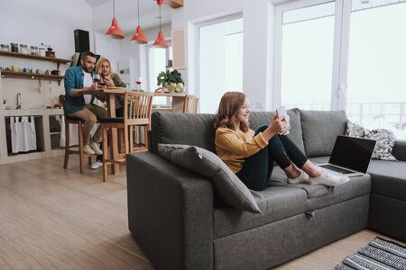 Family spending time at home and using smartphones Stock Photo