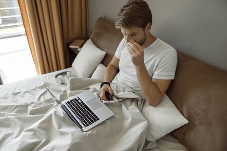 Man working remotely inspite of having cold 版權商用圖片