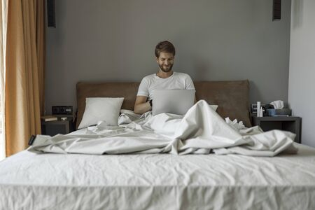 Smiling man working remotely from his bed 版權商用圖片