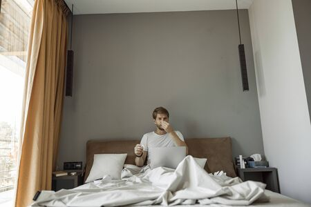 Man being affected by cold sitting in his bed
