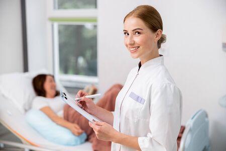 Glücklicher Arzt hält Formular für Patienten Standard-Bild