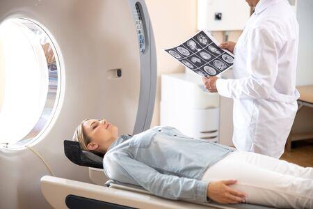 Junge Dame, die nach dem Tomographietest im Krankenhaus auf dem CT-Scannertisch liegt Standard-Bild
