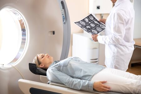 Señorita acostada sobre la mesa del escáner CT después de la prueba de tomografía en el hospital Foto de archivo