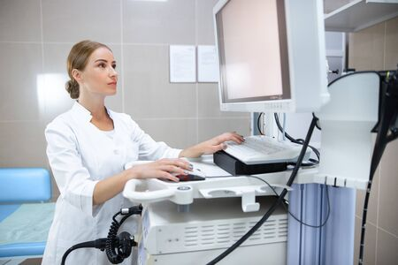 Female doctor using computer for diagnosis in office stock photo