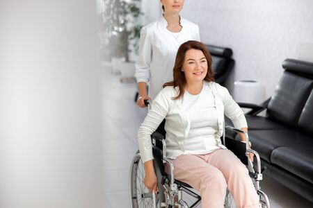 Merry lady going on wheelchair in hospital stock photo