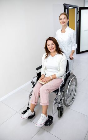 Disabled woman and nurse in clinic stock photo