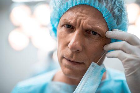 Cerca del doctor cansado frunciendo el ceño y tocando su frente Foto de archivo