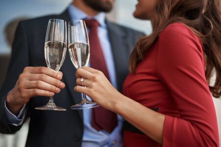 Man and woman celebrating with champagne glasses outdoor