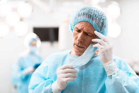 Tired doctor touching his head while standing with his eyes closed Stock fotó