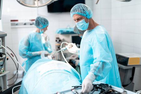 Highly qualified surgeon using laparoscope during surgical operation